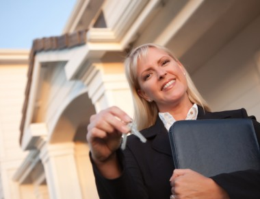 Female Real Estate Agent Handing Over Keys in Front of Beautiful House.